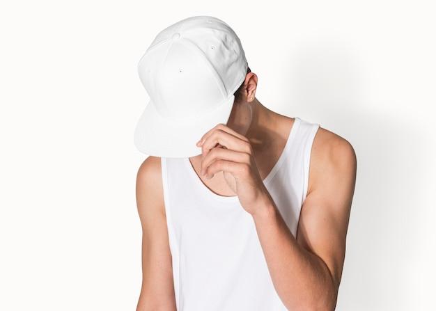Teenager in weißer hysteresenmütze und tanktop street fashion shooting