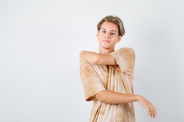 Teenager-junge, der die arme im t-shirt ausdehnt und selbstbewusst aussieht. vorderansicht.
