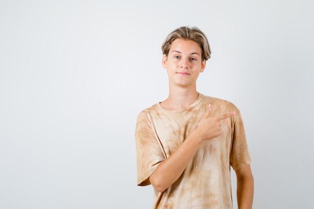 Teenager-junge, der nach rechts im t-shirt zeigt und selbstbewusst aussieht, vorderansicht.