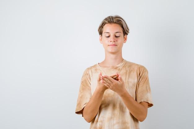 Teenager-junge, der vorgibt, etwas im t-shirt zu sehen und zufrieden aussieht. vorderansicht.