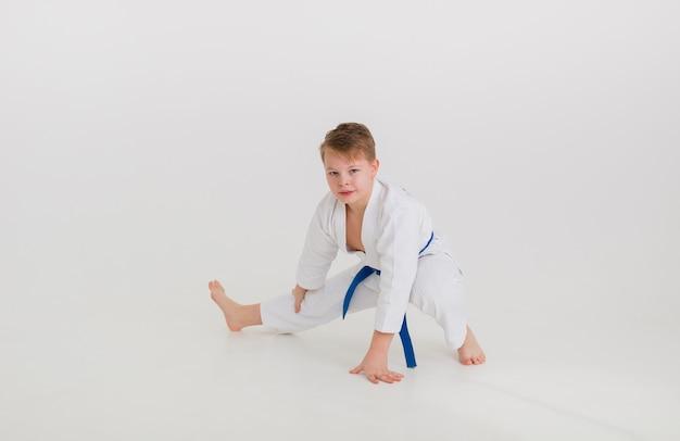 Teenager-junge in einem weißen kimono mit einem blauen gürtel macht eine strecke auf einer weißen wand