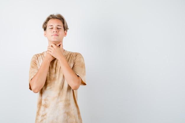 Teenager junge leidet unter halsschmerzen im t-shirt und sieht krank aus. vorderansicht.