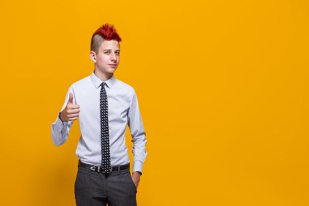 Teenager-junge über isolierter gelber wand, die positive geste mit hand daumen hoch tut