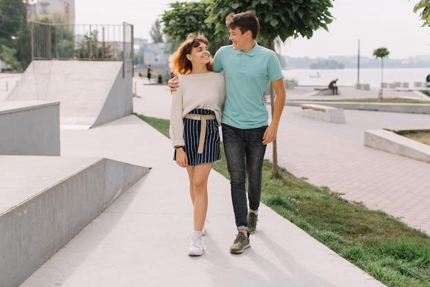 Teenager, junge und mädchen zwei im park und reden und scherzen.