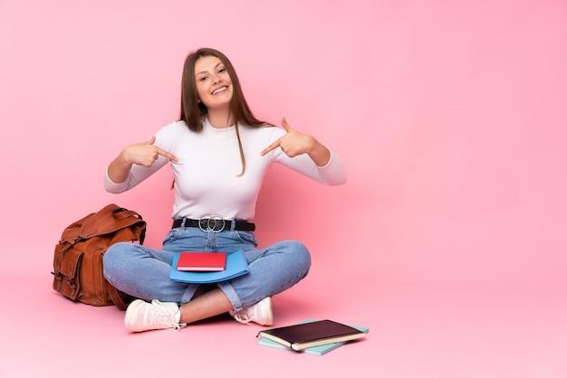 Teenager kaukasische studentin sitzen auf dem boden isoliert auf rosa wand stolz und selbstzufrieden