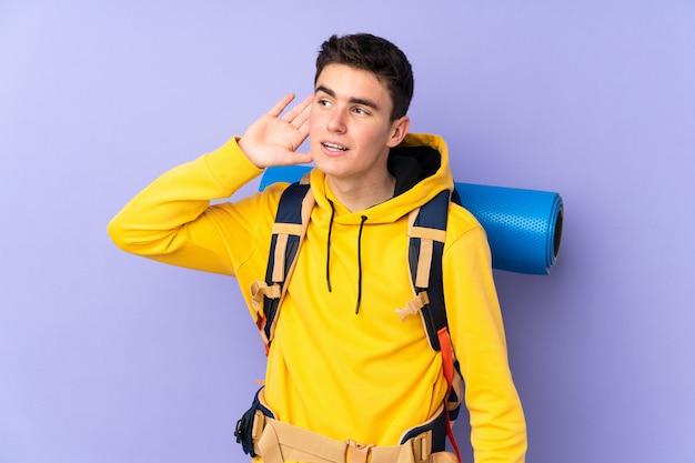 Teenager kaukasischer bergsteigermann mit einem großen rucksack auf lila wand, die etwas hört
