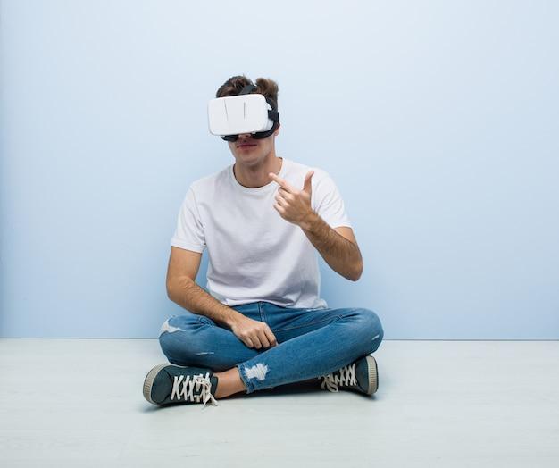 Teenager kaukasischer mann, der eine virtuelle realitätsbrille verwendet, die auf dem boden sitzt