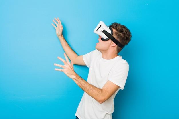 Teenager kaukasischer mann, der eine virtuelle realitätsbrille verwendet