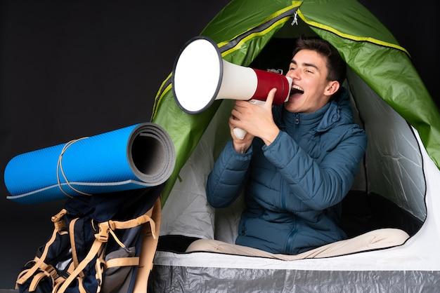 Teenager kaukasischer mann innerhalb eines campinggrünzeltes lokalisiert auf schwarz