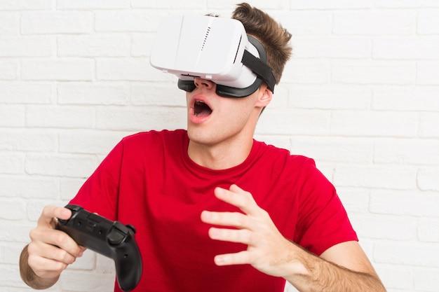 Teenager kaukasischer mann mit virtual-reality-brille und game-controller