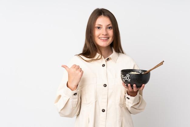 Teenager kaukasisches mädchen lokalisiert auf weißer wand, die zur seite zeigt, um ein produkt zu präsentieren, während eine schüssel nudeln mit essstäbchen hält