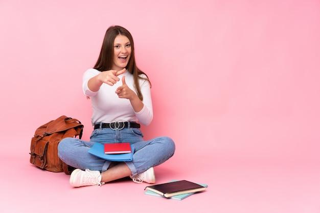 Teenager kaukasisches studentenmädchen, das auf dem boden lokalisiert auf rosa wand zeigt, zeigt nach vorne und lächelt