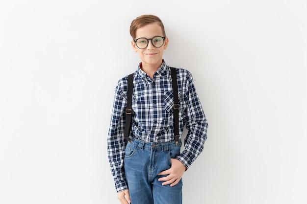 Teenager, kinder und modekonzept - kind gekleidet im karierten hemd, das über weißer wand aufwirft
