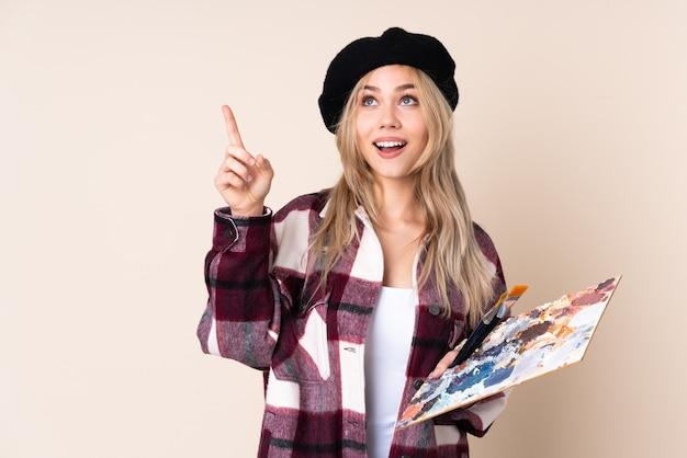 Teenager-künstlermädchen, das eine palette lokalisiert auf blauer wand hält, die mit dem zeigefinger eine große idee zeigt