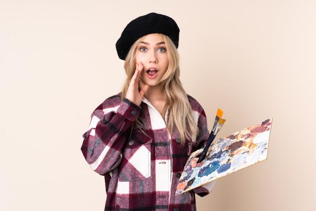 Teenager-künstlermädchen, das eine palette lokalisiert auf blauer wand mit überraschung und schockiertem gesichtsausdruck hält
