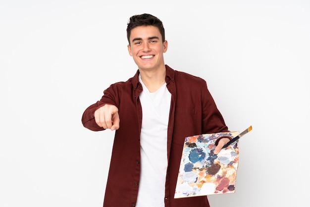 Teenager-künstlermann, der eine palette lokalisiert auf weißer wand hält, zeigt finger auf sie mit einem selbstbewussten ausdruck