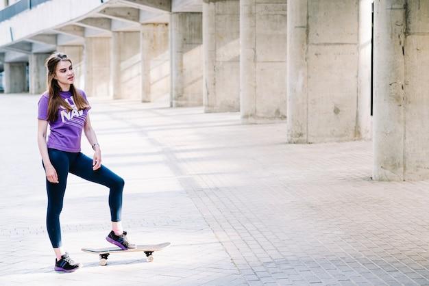Teenager landet ihren fuß auf ihrem skateboard