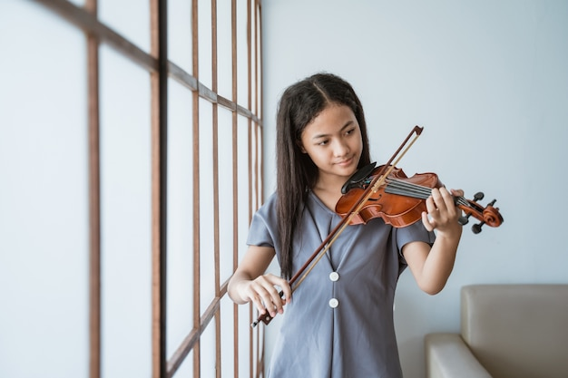 Teenager lernt, ein geigeninstrument zu spielen