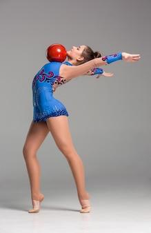 Teenager macht gymnastikübungen mit rotem gymnastikball auf grauem hintergrund