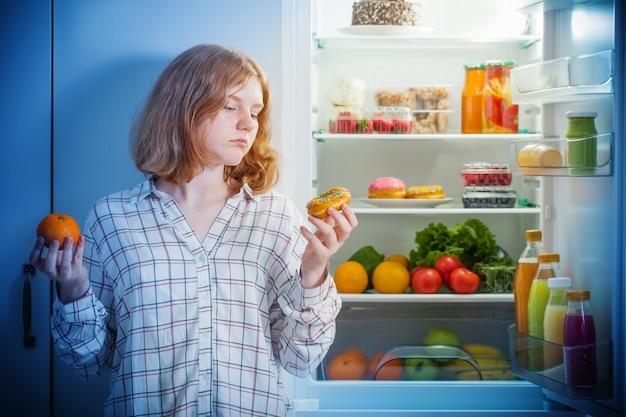 Teenager-mädchen am kühlschrank mit essen
