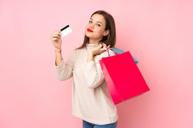 Teenager-mädchen auf rosa, das einkaufstaschen und eine kreditkarte hält