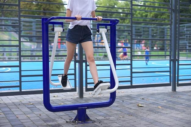 Teenager-mädchen auf sport-outdoor-simulator, aktiver gesunder lebensstil von teenagern, städtische sportplätze