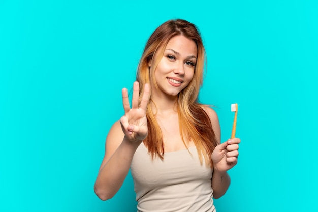 Teenager-mädchen beim zähneputzen isoliert auf blauem hintergrund glücklich und zählt drei mit den fingern