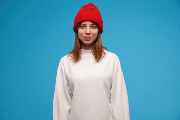 Teenager-mädchen, cool aussehende frau mit brünetten haaren. tragen eines weißen pullovers und eines roten hutes. menschen und emotionales konzept.