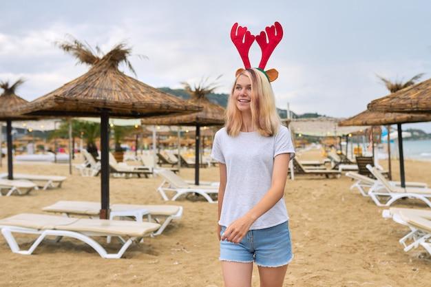 Teenager-mädchen, das auf dem strand in weihnachten mit hirschohren geht