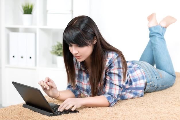 Teenager-mädchen, das auf laptop liegt, der zu hause auf sofa liegt