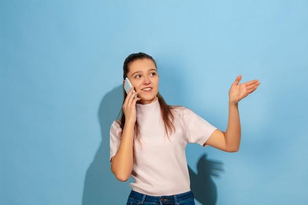 Teenager-mädchen, das auf smartphone spricht und lächelt