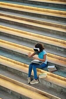 Teenager-mädchen, das auf stufen mit büchern und laptop sitzt und virtuelle geality-anwendung testet, die sie erstellt hat