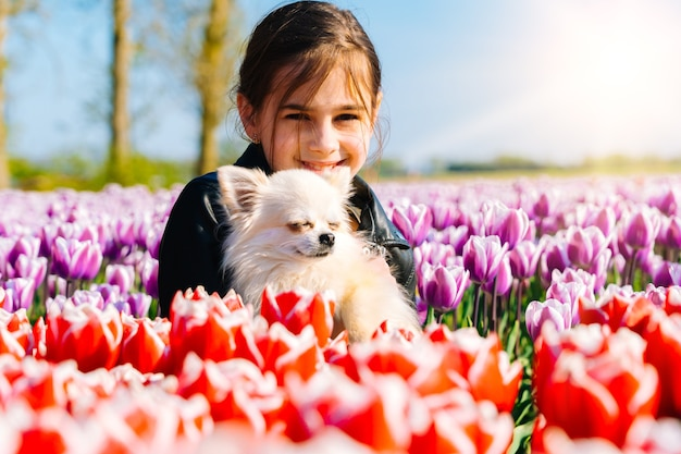 Teenager-mädchen, das auf tulpenfeldern in der region amsterdam, niederlande sitzt. magische niederländische landschaft mit tulpenfeld