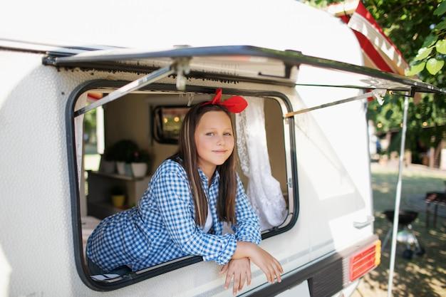 Teenager-mädchen, das aus dem fenster des wohnmobils späht