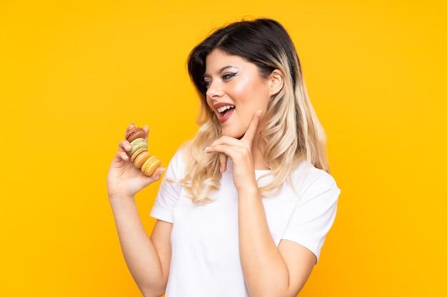 Teenager-mädchen, das bunte französische macarons hält und eine idee denkt