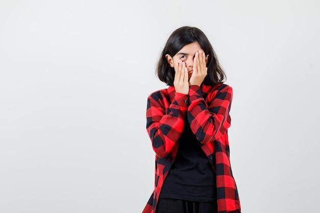 Teenager-mädchen, das das auge mit der hand bedeckt, während sie ihre haut in t-shirt, kariertem hemd herunterzieht und gelangweilt aussieht. vorderansicht.