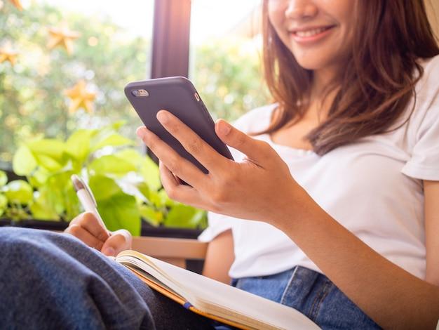 Teenager-mädchen, das das telefon benutzt und notizen entspannte haltung mit einem lächeln macht. vintage ton