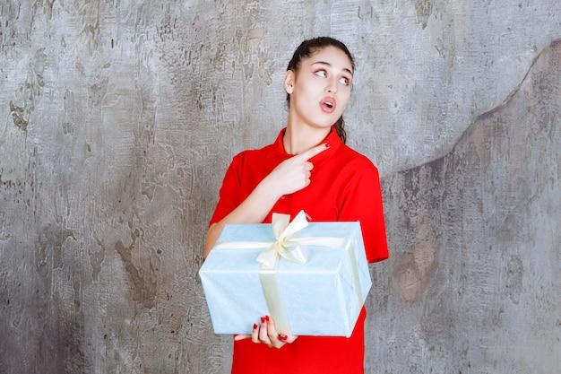 Teenager-mädchen, das eine blaue geschenkbox hält, die mit weißem band umwickelt ist und auf jemanden zeigt