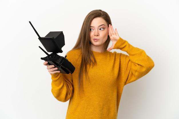 Teenager-mädchen, das eine drohnen-fernbedienung über isoliertem weißem hintergrund hält und etwas hört, indem es die hand auf das ohr legt