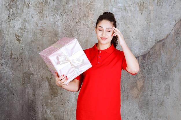 Teenager-mädchen, das eine rosa geschenkbox hält, die mit weißem band umwickelt ist und nachdenklich aussieht.
