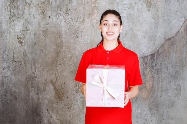 Teenager-mädchen, das eine rosa geschenkbox hält, die mit weißem band umwickelt ist.
