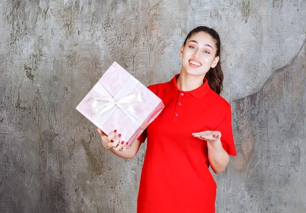 Teenager-mädchen, das eine rosafarbene geschenkbox hält, die mit weißem band umwickelt ist und die person im voraus anruft, um sie zu präsentieren.