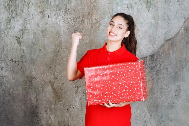 Teenager-mädchen, das eine rote geschenkbox mit weißen punkten darauf hält und ihre faust zeigt