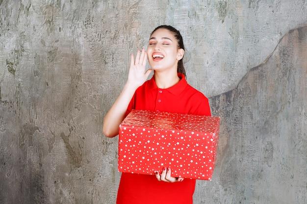 Teenager-mädchen, das eine rote geschenkbox mit weißen punkten darauf hält und nach jemandem ruft