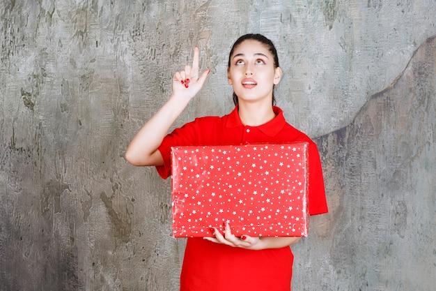 Teenager-mädchen, das eine rote geschenkbox mit weißen punkten darauf hält und nach oben zeigt