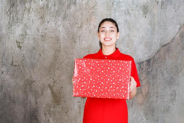 Teenager-mädchen, das eine rote geschenkbox mit weißen punkten darauf hält.