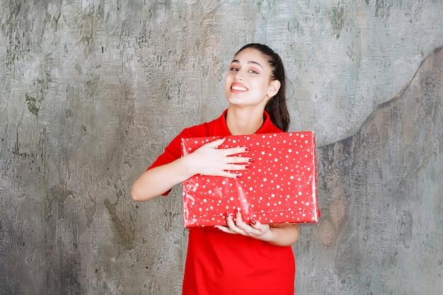 Teenager-mädchen, das eine rote geschenkbox mit weißen punkten darauf hält