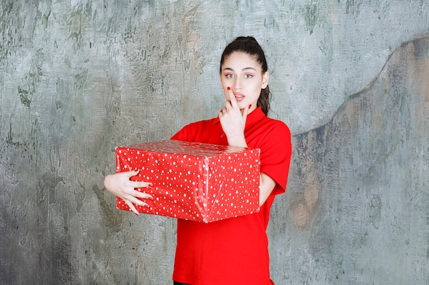 Teenager-mädchen, das eine rote geschenkbox mit weißen punkten hält und nachdenklich aussieht.