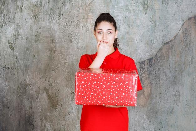 Teenager-mädchen, das eine rote geschenkbox mit weißen punkten hält und verängstigt und verängstigt aussieht.