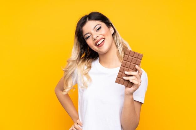 Teenager-mädchen, das eine schokoladentafel in einer hand und einen apfel in der anderen nimmt